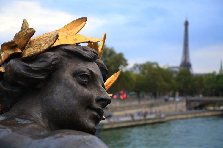 Una escultura del puente Alexander III de París con la torre Eiffel de fondo