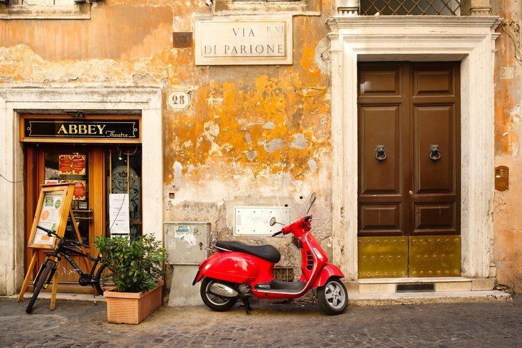 Tradicional calle romana con la típica moto 'vespa'